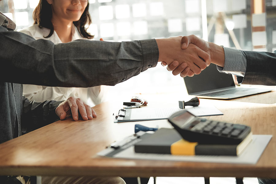About - Closeup Of Agent Shaking Hands With Client
