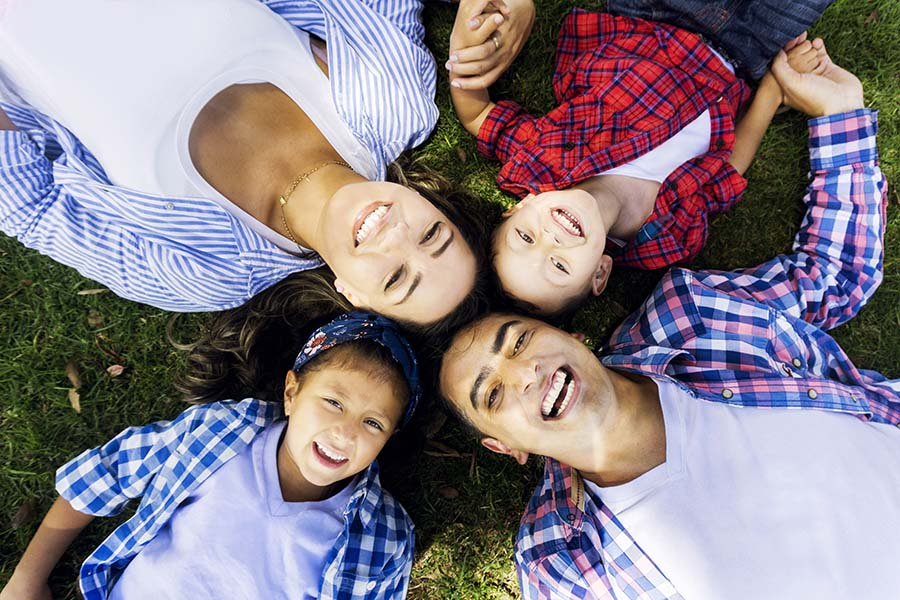 Blog - Happy Latino Family Laying On Grass